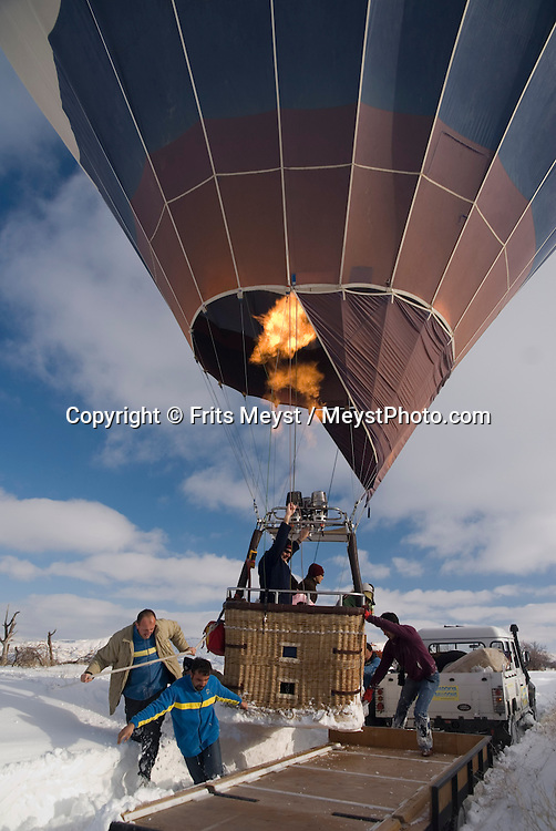 Goreme, Nevsehir, Cappadocia, Turkey.  With a hot air balloon of Kapadokya Balloons we glide over the valleys of Goreme National Park. A fresh pack of snow has turned the winter landscape into an even bigger fairy tale. Photo by Frits Meyst/Adventure4ever.com