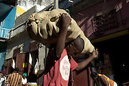 A worker carries a heavy load in the central market. Cap Haitian, January 26, 2008.