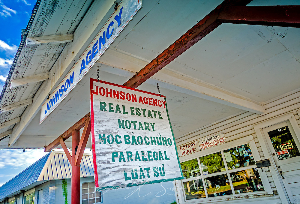 Signs in English and Vietnamese advertise the real estate and notary public services offered by Johnson Agency, Aug. 15, 2015, in Bayou La Batre, Alabama. (Photo by Carmen K. Sisson/Cloudybright)