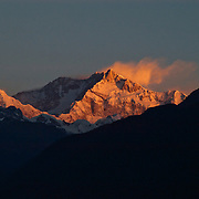 """Kangchenjunga - the world's third highest peak, whose name means """"Five Treasure Houses of Snow"""" - glows at sunset from the village of Pelling, West Sikkim, India."""