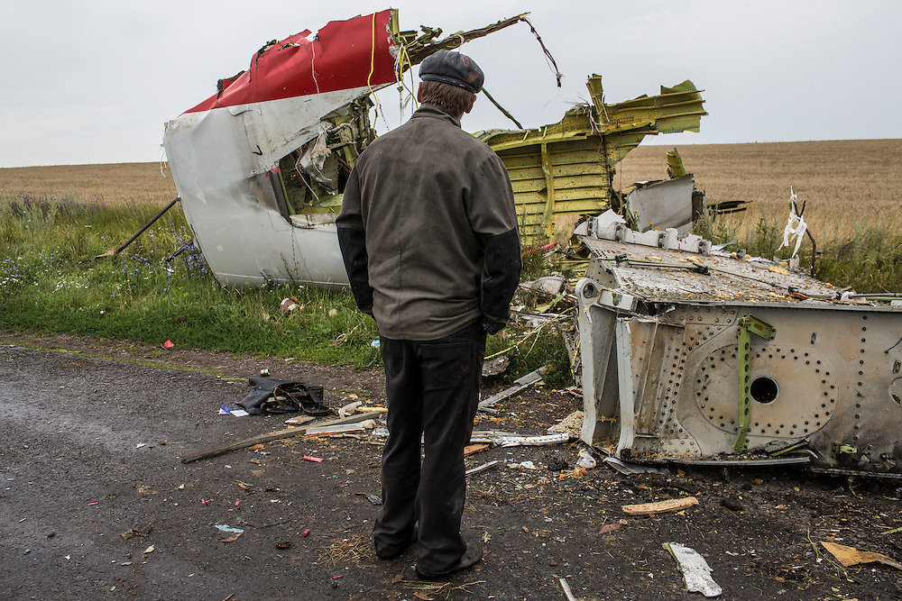 GRABOVO, UKRAINE - JULY 18: A man looks at the wreckage of a commercial passenger plane which was shot from the sky by a missile the previous day on July 18, 2014 in Grabovo, Ukraine. Malaysia Airlines flight MH17 travelling from Amsterdam to Kuala Lumpur has crashed on the Ukraine/Russia border near the town of Shaktersk. The Boeing 777 was carrying 280 passengers and 15 crew members. (Photo by Brendan Hoffman/Getty Images) *** Local Caption ***