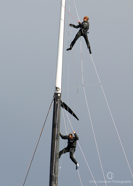 A crewman is sent aloft to help a United Internet Team Germany sailor who had been swung like a rag doll after losing his grip up the mast of GER72. Louis Vuitton Act 6. Malmo, Sweden. 26/8/2005