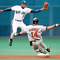 Toronto Blue Jays shortstop Tony Batista jumps to snare an errant throw while trying to turn the double play against Baltimore.<br />