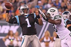 Aug 26, 2012; East Rutherford, NJ, USA; Carolina Panthers quarterback Cam Newton (1) throws a pass while being rushed by New York Jets defensive end Quinton Coples (98) during the first half at MetLife Stadium.
