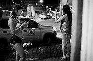 """Lara Santos and Karol. Lara exchange messages with a client while Karol waves to a car. In Campinas the dress code requires showing more body, unlike what happens in São Paulo. To """"meet"""" clients in this street, they must pay a commission to a woman who runs it."""