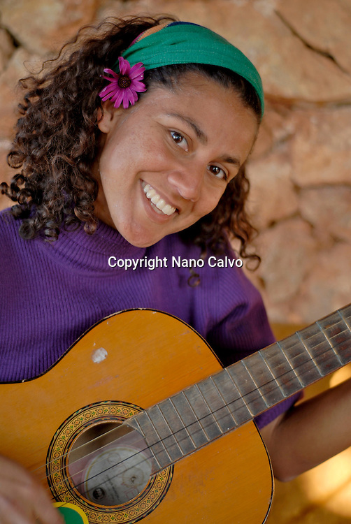 Attractive young brazilian woman plays the guitar at Greenheart´s La Casita Verde, Ibiza