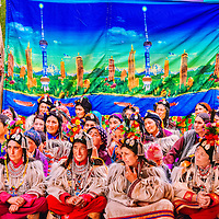 A section of women in traditional dresses, sitting in front of a background featuring modern high-rise buildings,  enjoying a local festival in Ladakh. The women in the front row, dressed in their fully traditional attire, waiting for their turn to dance as they are among the participants themselves.