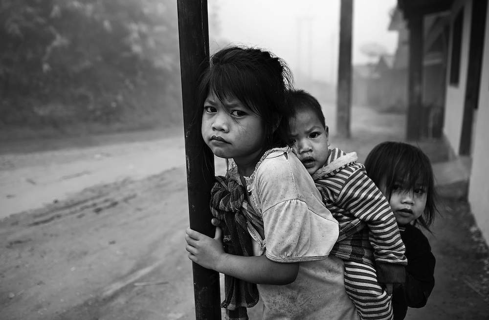 A Khamu girl caring for children in her mountain village near Luang Prabang, Laos.