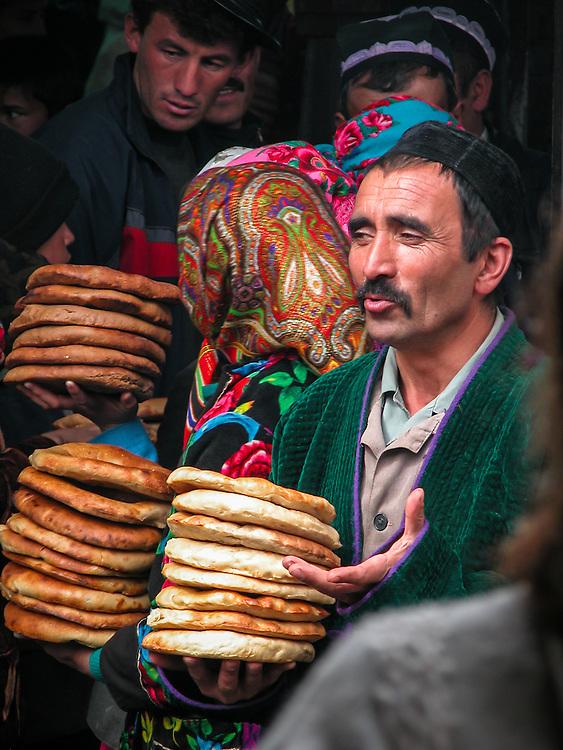 Portrait of a Tajik man selling flat bread (non) loaves in a market in western Tajikistan