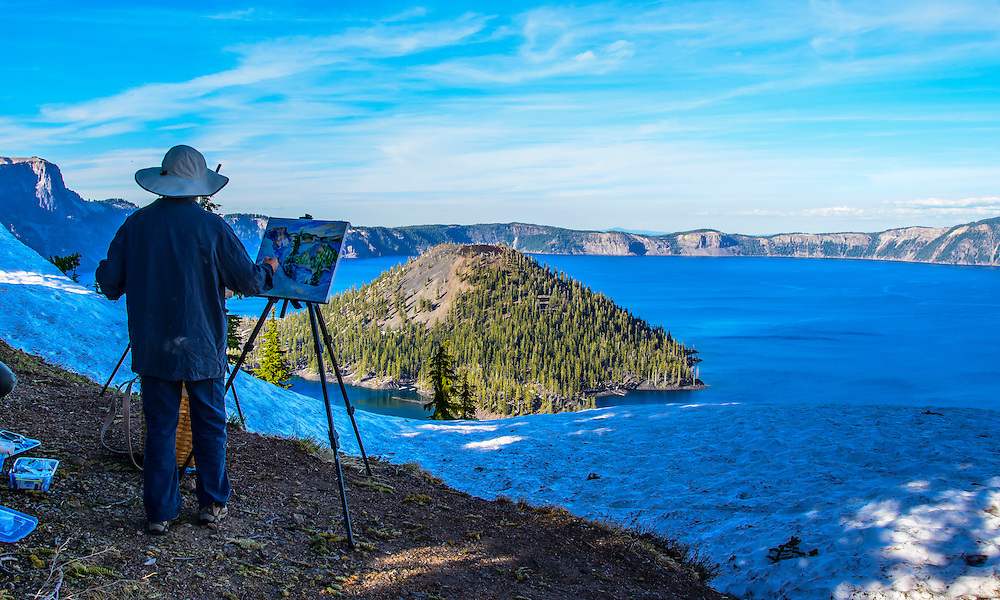 Nature's art is being painted by a local artist. The waters of Crater Lake really look ink blue.<br /> The ink blue color is the only color not absorbed by the deep ultra transparent water.  It  is the deepest lake in the USA. Crater Lake National Park, Oregon.
