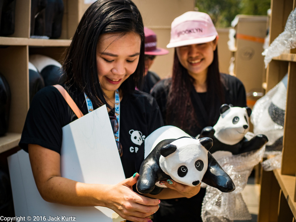 "04 MARCH 2016 - BANGKOK, THAILAND: Volunteers hold paper maché pandas before setting them out for the ""1600 Pandas+ World Tour in Thailand: For the World We Live In and the Ones We Love"" exhibit Friday at Sanam Luang in Bangkok. The 1600 paper maché pandas, an art installation by French artist Paulo Grangeon will travel across Bangkok and parts of central Thailand for the next week and then will be displayed at Central Embassy, a Bangkok shopping mall, until April 10. The display of pandas in Thailand is benefitting World Wide Fund for Nature - Thailand and is sponsored by Central Embassy with assistance from the Tourism Authority of Thailand and Bangkok Metropolitan Administration and curated by AllRightsReserved Ltd.     PHOTO BY JACK KURTZ"