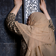 A woman presses herself against the Quranic writing in the Jammia Masjid in Srinagar for the blessing.