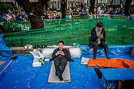 Low men in the company hierarchy have been sent to Ueno Park to guard their company's spot until their colleagues can finish work and head to the o-hanami cherry blossom celebration.  Tokyo, Japan.