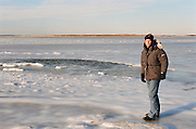 man in Winter clothing standing by a frozen bay in Montauk, NY