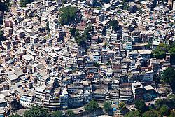 Rio de Janeiro visto de cima. A Rocinha eh um bairro-favela localizado na cidade do Rio de Janeiro, no Brasil. Destaca-se por ser uma das maiores favelas da cidade, contando com cerca de 60 mil habitantes..Eh vizinha a um shopping center, entre os bairros da Gavea e de Sao Conrado, dois dos bairros com o IPTU mais alto da cidade. A proximidade entre as residencias de classe alta desses dois bairros e as de baixa e pobre da Rocinha marca um profundo contraste urbano na paisagem da regiao / Rocinha is the largest favela in Rio de Janeiro. It is located in Rio's South Zone, between the districts of Sao Conrado and Gavea. It is built on a steep hillside overlooking the city, just one kilometre from the beach.