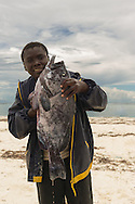 This young boy was more than happy to show off his large fish before taking it to the market to sell.