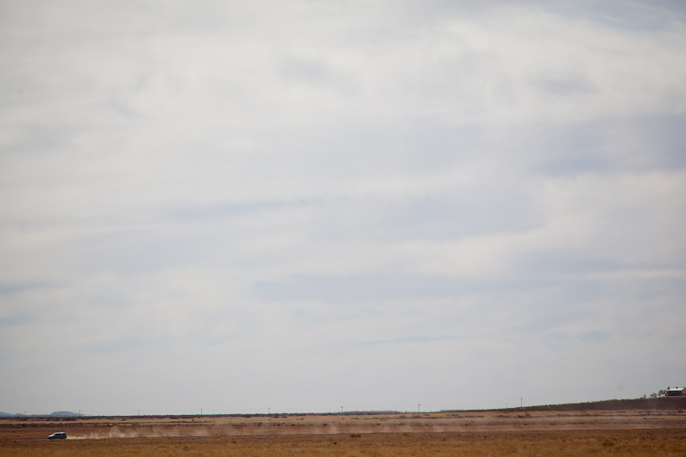 A car is seen driving north from across the desert in Columbus, New Mexico. Recently federal authorities arrested the mayor, police chief, and trustees who were allegedly operating an illegal gun running ring.