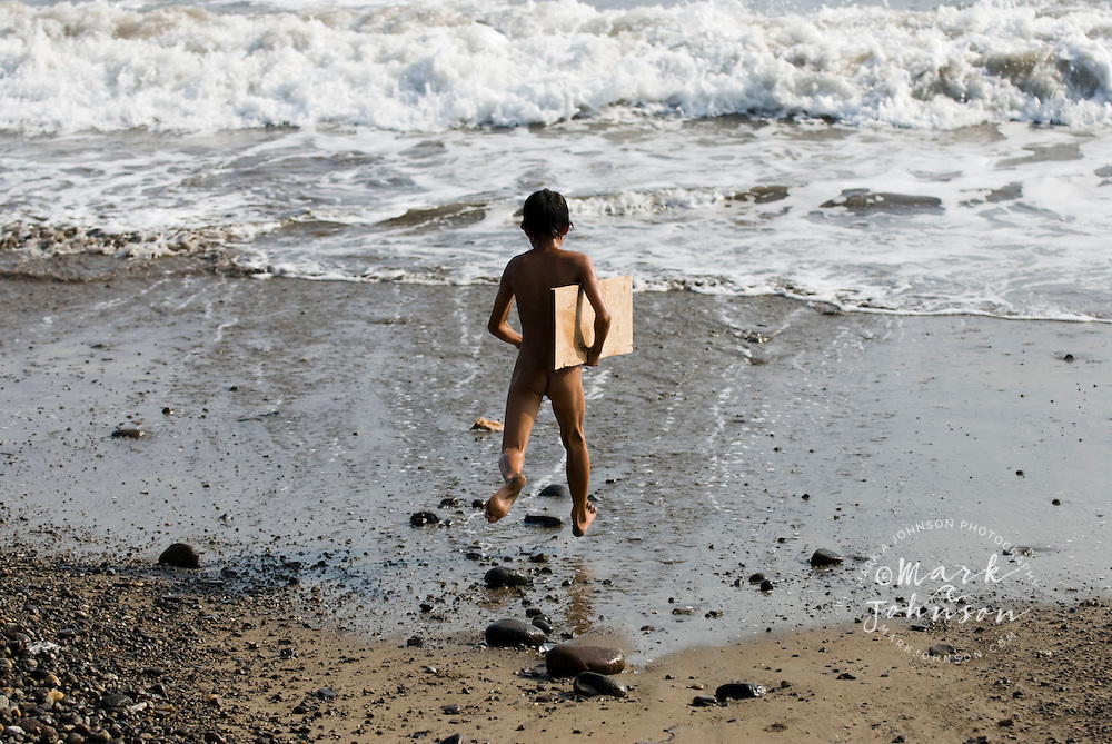 "Boy running on beach with ""surfboard"", a plywood plank, S. Sumatra, Indonesia"