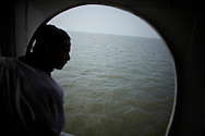 The captain of a ferry is watching the Meghna river.?This area in the south of Bangladesh has been called ground zero of climate-change due to heavy river and ocean erosion. The lowlying area is also hugely affected by cyclones and rising sea-levels...By the Mouth of Ganges, at the Bay of Bengal is the Island of Bhola. This home of about two million people is considered to be ground zero of climate change. Half the island has disappeared in the past 40 years, and according to scientists the pace is not going to slow down. People pack up and leave as the water get closer. Some to a nearby embankment, while those with enough money move further inland, but for most life move on until the inevitable. It's always about survival for the people in one of the worlds poorest countries...Photo by: Eivind H. Natvig/MOMENT