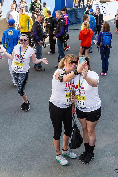 Boston Marathon: BAA 5K road race, fans take pictures at marathon finish line