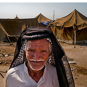 An Iraqi man stands near his tent home in the al-Manathera IDP camp located 20 kilometers south of the Iraqi city of An-Najaf September 20, 2007. Opened in February for 10-15 families, the camp now has swollen to 230 mostly Shia families displaced by sectarian violence in Baghdad, Falluja, and Diyala province. The families living here are dependent now on the aid of the Iraqi Red Crescent and the UNHCR.