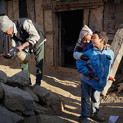 Sushil, 7, kisses his youngest sister, 11-month-old Kusum, in front of their temporary home.<br />