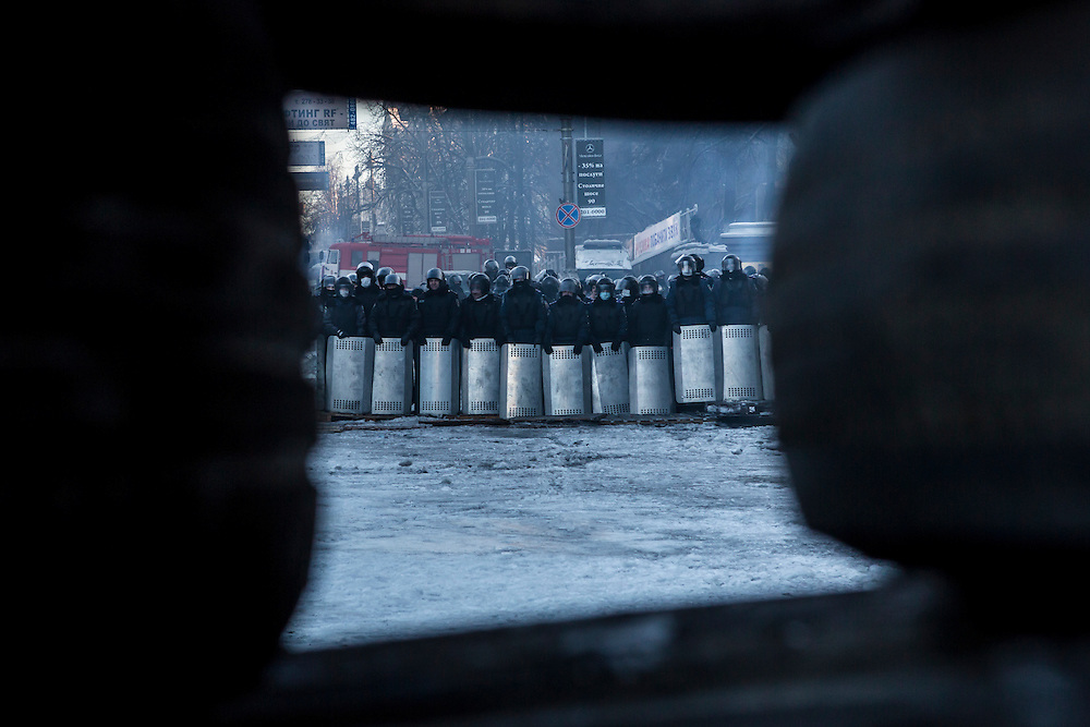 KIEV, UKRAINE - JANUARY 24: A line of police officers near Dynamo stadium is visible through a wall of tires on January 24, 2014 in Kiev, Ukraine. After two months of primarily peaceful anti-government protests in the city center, new laws meant to end the protest movement have sparked violent clashes in recent days. (Photo by Brendan Hoffman/Getty Images) *** Local Caption ***