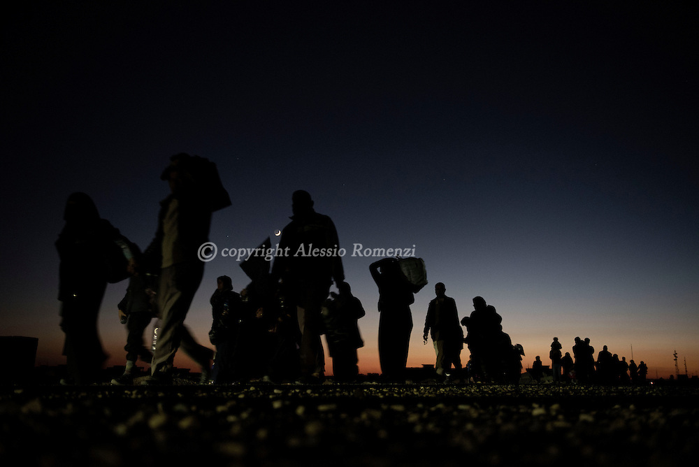 Iraq, Bazwaia: Iraqi civilians, who fled the fight against jihadists of the Islamic State group in the city of Mosul, walk at sunset, as they head to camps housing displaced people on November 2, 2016. Alessio Romenzi