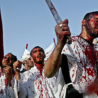 Covered in blood and holding swords Shiite Muslims mark the Ashoura outside of the Imam Hussein holy shrine in Karbala, Iraq. The Shiite holy month of Muharam reached its climax on Tuesday, its 10th day, when pilgrims reenacted the decapitation of the Imam Hussein at the battle of Karbala, when he and his 72 followers were lured into a trap and slaughtered by the Caliph Yazid's army. March 2004.