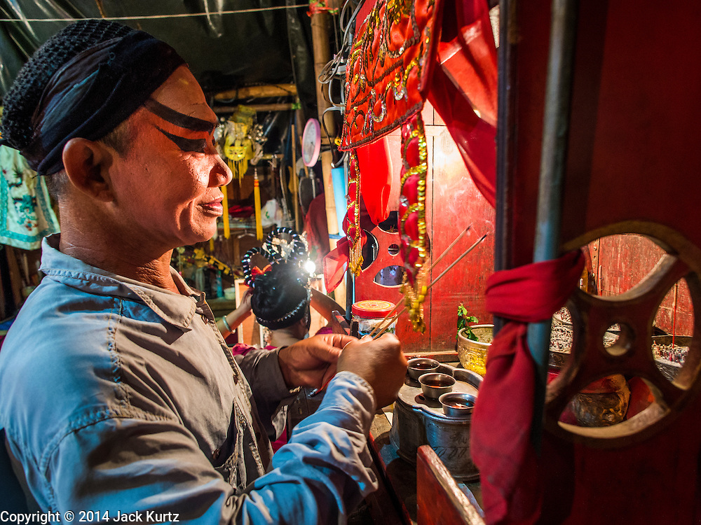 "18 AUGUST 2014 - BANGKOK, THAILAND: A  member of the Lehigh Leng Kaitoung Opera troupe prays backstage before a performance at Chaomae Thapthim Shrine, a small Chinese shrine in a working class neighborhood of Bangkok. The performance was for Ghost Month. Chinese opera was once very popular in Thailand, where it is called ""Ngiew."" It is usually performed in the Teochew language. Millions of Chinese emigrated to Thailand (then Siam) in the 18th and 19th centuries and brought their culture with them. Recently the popularity of ngiew has faded as people turn to performances of opera on DVD or movies. There are still as many 30 Chinese opera troupes left in Bangkok and its environs. They are especially busy during Chinese New Year and Chinese holiday when they travel from Chinese temple to Chinese temple performing on stages they put up in streets near the temple, sometimes sleeping on hammocks they sling under their stage. Most of the Chinese operas from Bangkok travel to Malaysia for Ghost Month, leaving just a few to perform in Bangkok.     PHOTO BY JACK KURTZ"