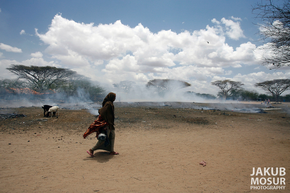 September 14, 2006 - Somali refugee walks past burning refuse at the Dagahaley Refugee Camp in Dadaab, Kenya, 50 miles from the Somali border. Somalis are fleeing from recent clashes between Somalia Union of Islamic Courts and Somali warlords. Over 21,000 refugees since January 2006 have arrived in Dadaab which has a growing population of 140,000 refugees, in the North Eastern province of Kenya..(Photo by Jakub Mosur/Polaris)