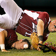 June 17, 2009; Omaha, NE, USA; Arkansas Razorbacks Ryan Cisterna (left) and first baseman Andy Wilkins (17) flip over chasing a foul ball in the 12th inning against the Virginia Cavaliers during game nine of the College World Series at Rosenblatt Stadium. Mandatory Credit: Crystal LoGiudice-US PRESSWIRE ..