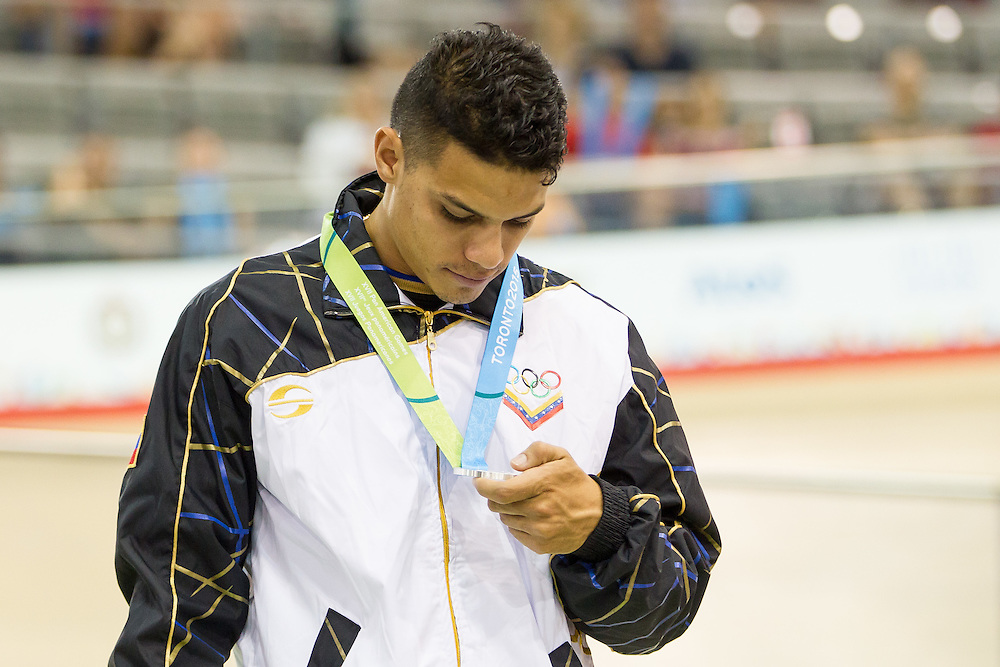 Manuel  Canelon Vera of Venezuela looks at his silver medal during the medal ceremony for the men's cycling keirin at the 2015 Pan American Games in Toronto, Canada, July 19,  2015. Cannon Vera learned earlier in the day that a close personal and training partner was killed in a cycling accident with a car yesterday.<br /> AFP PHOTO/GEOFF ROBINS