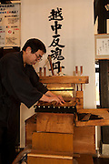 """TOYAMA MEDICINE.Demonstration of traditional way of making pills at IKEDAYA YASUBEI SHOTEN a traditional medicine shop in Toyama city. Ikedaya-Yasubei Shoten preserves the atmosphere of a time-honored herbal medicine shop. """"Ecchu-hangontan"""" written on it's front sign is said to be a miracle medicine that reinvigorates one's body. In the shop, visitors can watch a demonstration of making pills by using the traditional hand-operated pill maker. On the 2nd floor of the shop is the restaurant YAKUTO where healthy dishes made with Chinese herbal medicines are served. http://www.hangontan.co.jp/Toyama prefecture is located near the center of Japan and is approximatelythe same distance from the three largest cities in Japan-Tokyo,Nagoya,andOsaka. Toyama's pharmaceutical tradition has a more than 300 years history. As it is located on the Japan sea, it is facing China and has been an importer of traditional Chinese medicine knowledge which it developed through the years. There are now approximately 100 manufactures and over 100 factories in Toyama in terms of pharmaceutical products and Toyama prefecture acquires a steady reputation as Japan's medicine manufacturing base."""