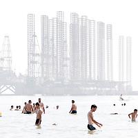 USE ARROWS &larr; &rarr; on your keyboard to navigate this slide-show<br /> <br /> Baku, Azerbaijan, 24 July 2012<br /> Azeri people swim beside an oil extraction platform in Baku.<br /> Photo: Ezequiel Scagnetti