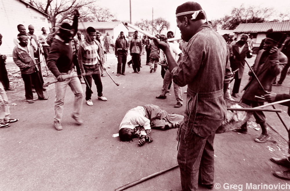 Inkatha Freedom Party supporters kill a man they accused of shooting at them in Nancefield hostel, Soweto, August, 1990. The worker's hostels were ethnically cleansed of non Zulus.