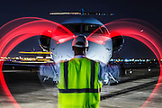 Using high visibility red wands, a lineman simulates waving an aircraft into parking position at night.