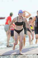 Young woman exiting triathlon swim stage.