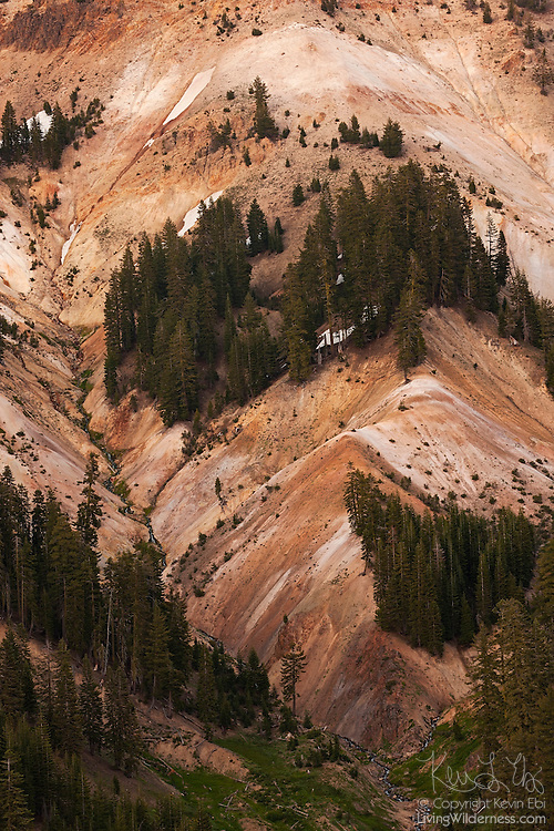 A colorful hillside shows the volcanic activity near Bumpass Hell in Lassen Volcanic National Park, California. The colors are the result of sulfuric acid diluted by rain and snowmelt. This weakened acid causes the volcanic rock to decompose at varying rates.