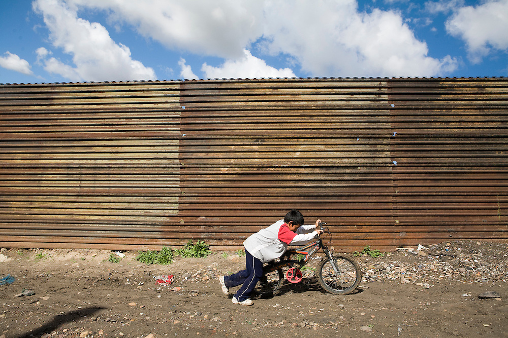 A boy pushes his bicycle along a metal fence separating Tijuana, Baja California, Mexico, from southern California in Tijuana on Monday, Feb. 4, 2008.