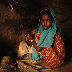 "Kadija's daughter Saidya, 11, prepares coffee inside their home near Barentu, Eritrea august 25, 2006. Kadija is a traditional birth assistant as well as a recipient of a donkey from the women's union ""Hamade"". (Ami Vitale)"