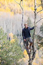 male hiker up in an Aspen Tree looking at the sunset in Santa Fe, NM