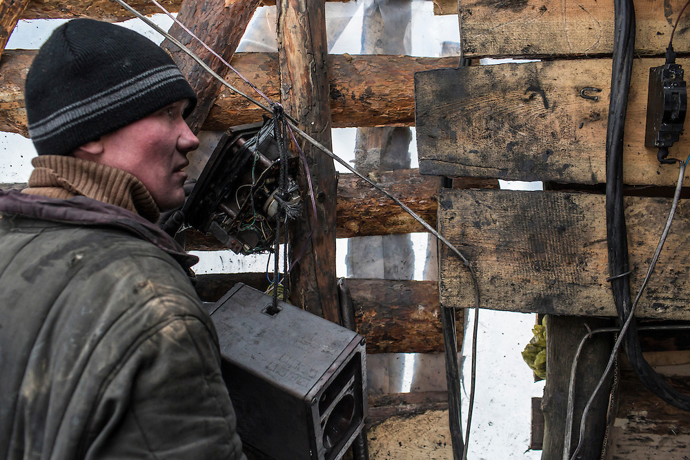 SNEZHNE, UKRAINE - JANUARY 25, 2015: Dmitry Kontratenko, who works at a small private coal mine, talks on the radio to miners working down in the mine in Snezhne, Ukraine. The mine produces approximately 15 tons of coal per day with a crew of four men. CREDIT: Brendan Hoffman for The New York Times