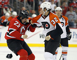 November 8, 2007; Newark, NJ, USA;  New Jersey Devils right wing Arron Asham (22) and Philadelphia Flyers left wing Riley Cote (32) fight during the first period at the Prudential Center in Newark, NJ.