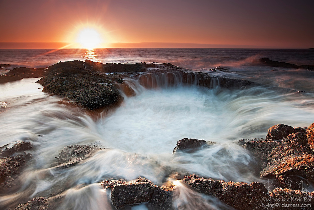 Water from the Pacific Ocean drains through the skylight of a sea cave at Cape Perpetua near Yachats, Oregon. During the year's highest tides or in strong surf, ocean waves splash onto the rocks and make a 360-degree waterfall as the water drains into the hole.