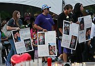 Family members of those killed in the Century theater shootings on July 20, 2012 carry posters honoring their relatives after  a prayer vigil for the victims in Aurora, Colorado July 22, 2012. REUTERS/Rick Wilking (UNITED STATES)
