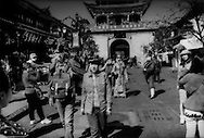 Tourism pandemonium in front of Dali's South Gate.  Yunnan, China.  2014  Although the Bai community of Dali has not been as affected by mass tourism to the degree that Lijiang has, the old city is largely vacated of its original Bai residents and given over to tourism commerce.