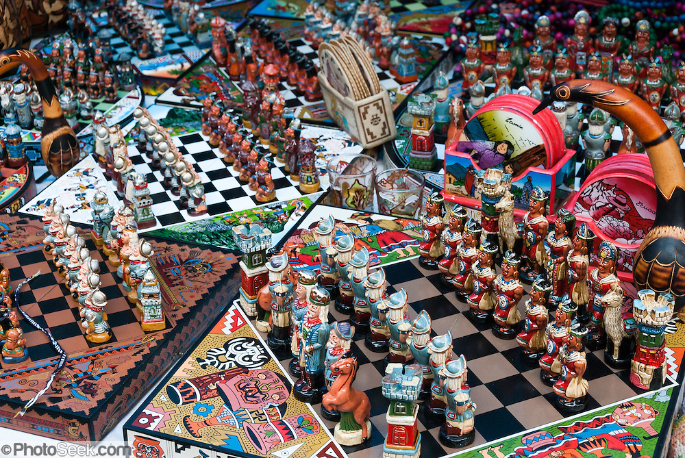Ecuadorian chess sets fight conquistadors versus Inca warriors in Otavalo, Ecuador, South America. The culturally vibrant town of Otavalo attracts many tourists to a valley of the Imbabura Province of Ecuador, surrounded by the peaks of Imbabura 4,610m, Cotacachi 4,995m, and Mojanda volcanoes. The indigenous Otavaleños are famous for weaving textiles, usually made of wool, which are sold at the famous Saturday market and smaller markets during the rest of the week. The Plaza del Ponchos and many shops tantalize buyers with a wide array of handicrafts. Nearby villages and towns are also famous for particular crafts: Cotacachi, the center of Ecuador's leather industry, is known for its polished calf skins; and San Antonio specializes in wood carving of statues, picture frames and furniture. Otavaliña women traditionally wear distinctive white embroidered blouses, with flared lace sleeves, and black or dark over skirts, with cream or white under skirts. Long hair is tied back with a 3cm band of woven multi colored material, often matching the band which is wound several times around their waists. They usually have many strings of gold beads around their necks, and matching tightly wound long strings of coral beads around each wrist. Men wear white trousers, and dark blue ponchos. Otavalo is also known for its Inca-influenced traditional music (sometimes known as Andean New Age) and musicians who travel around the world.