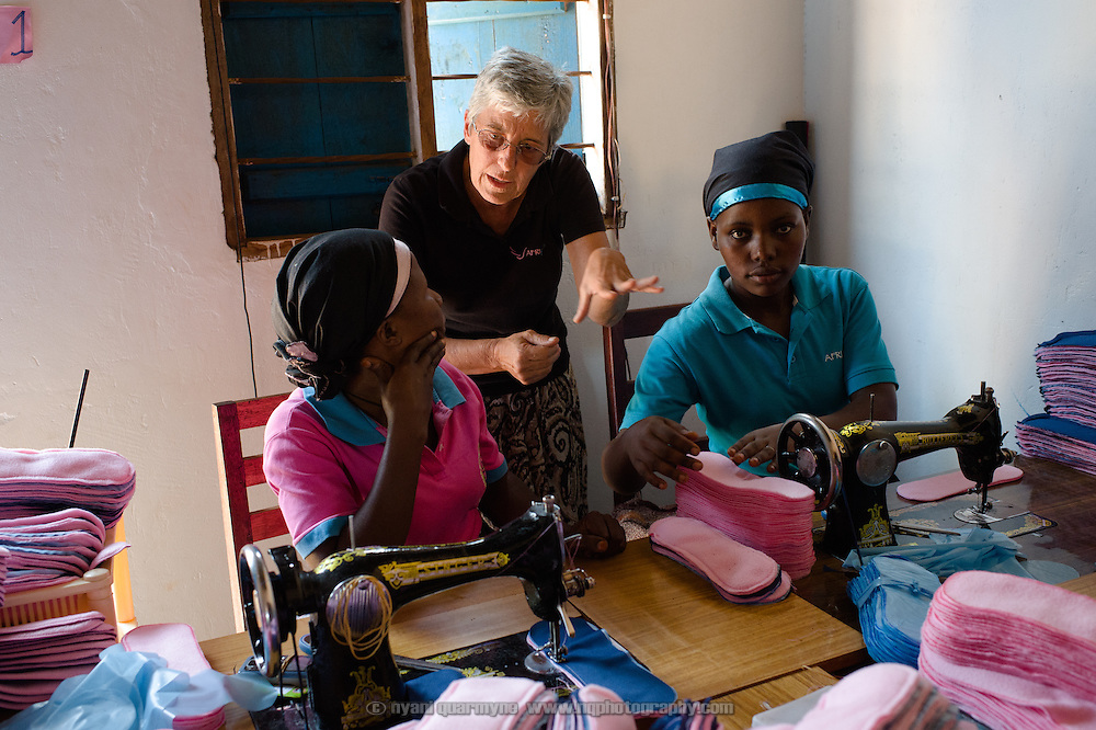Dorothy Maynard, a volunteer (at centre), with Annette Namale (left), and Bridget Nakuya at the Afripads factory in the village of Kitengeesa in the Central Region of Uganda on 30 July 2014.<br /> <br /> Started by volunteers in 2009, Afripads manufactures reusable fibre sanitary pads made locally by community residents. Beginning with a single employee, the company now employs roughly 100 women and produces approximately 700 kits (consisting of pads, holders and a bag) each week. At USh 12,000 to 15,0000 (&pound;2.75 to &pound;3.40) for a kit that lasts approximately one year, Afripads offer a significant saving over disposables which may cost in excess of USh 42,000 (&pound;9.60) over the course of a year. And for the many girls and women who cannot afford disposables, they offer an affordable and more hygienic alternative to rags, cotton wool or toilet paper, all of which are frequently used. At schools where Afripads have been distributed, teachers report that absenteeism has dropped sharply as girls who previously did not have access to proper sanitary pads now no longer stay home when they have their periods.