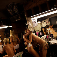 """Anya"" embraces a friend in the dressing room as girls prepare for her turn to dance at the world famous Mons Venus strip club in Tampa, Florida."